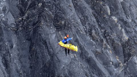 A rescue worker is lifted by helicopter from the crash site in the French Alps on March 26.