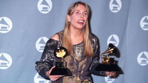 """Mitchell holds her two Grammys after the 1996 award ceremony in Los Angeles. She won the best pop album and best recording package awards for """"Turbulent Indigo."""""""