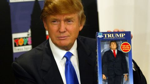 Trump poses with the new Donald Trump 12-inch talking doll on September 29, 2004, at the Toys 'R' Us store in New York City.