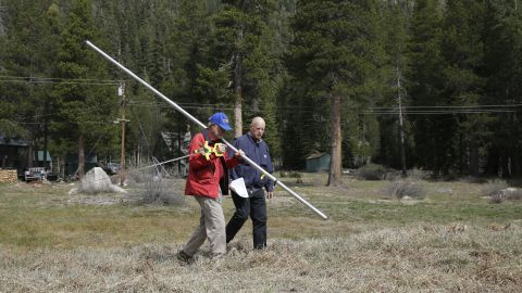 California Gov. Jerry Brown, right, walks with Frank Gehrke, chief of the California Cooperative Snow Surveys Program for the Department of Water Resources, near Echo Summit, California, in April. Gehrke said this was the first time since he has been conducting the survey that he found no snow at that location at that time of the year.