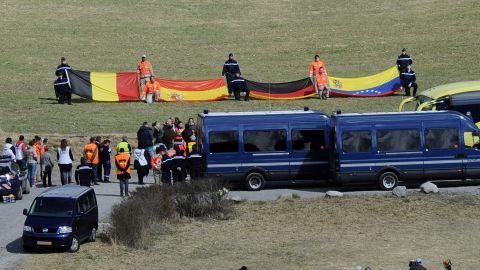 Relatives of the Germanwings  crash victims arrive on April 4, to attend a ceremony as rescuers hold flags of the late passengers' nationalities in the village of Le Vernet.