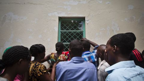 People in Garissa crowd around a mortuary window on April 4, 2015, to view the bodies of the alleged attackers. Authorities later paraded the bodies through a crowd on the bed of a pickup truck.