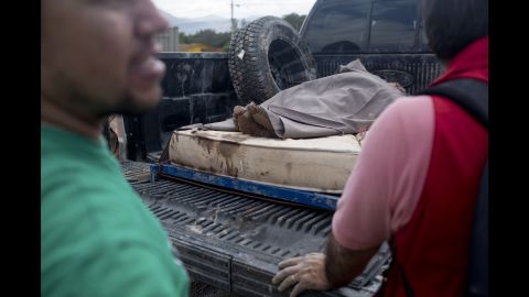 A woman rescued from the mud rests on a mattress in the back of a truck in Copiapo on March 26.