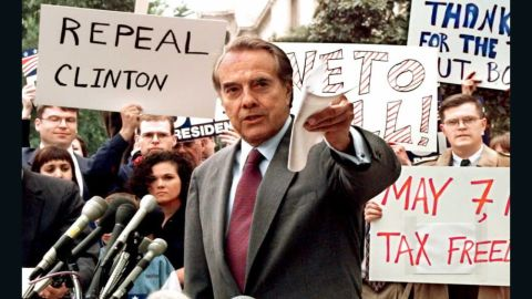 """Republican presidential candidate U.S. Senator Bob Dole (center) pushes for a repeal of the 4.3 cent gas tax during a rally in front of the Internal Revenue Service, as he campaigned against President Bill Clinton. Dole's campaign slogan was """"The Better Man for a Better America."""""""
