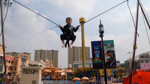 A child bounces on a trampoline at an outdoor entertainment area.