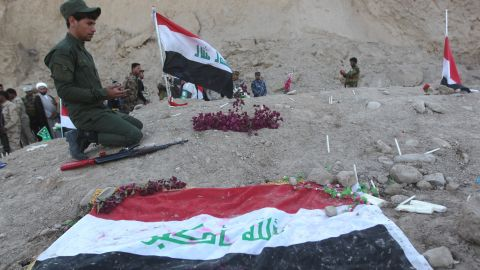 An Iraqi Shiite fighter and member of Iraq's Popular Mobilisation, prays at a burial site believed to hold victims of a June massacre in which hundreds of army cadets were executed by the Islamic State (IS) group, in the city of Tikrit, on April 4, 2015