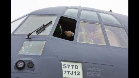 Lockheed Martin pilot Steve Knoblock points out features inside the cockpit of the MC-130J Super Hercules Commando II.