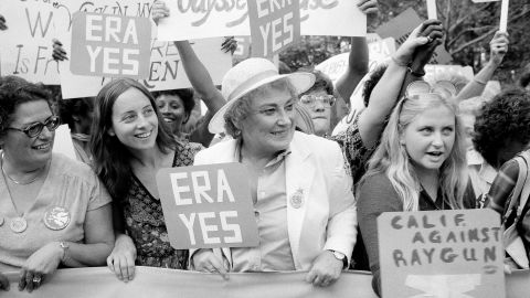 """Bella Abzug, center, smiles as she holds up an ERA sign on New York's Fifth Avenue in 1980 to celebrate the 60th anniversary of women receiving the right to vote. In its 1998 obituary, The New York Times called Abzug, who represented Manhattan in Congress in the 1970s, a """"founding feminist"""" and an icon of the movement, along with Betty Friedan and Gloria Steinem."""