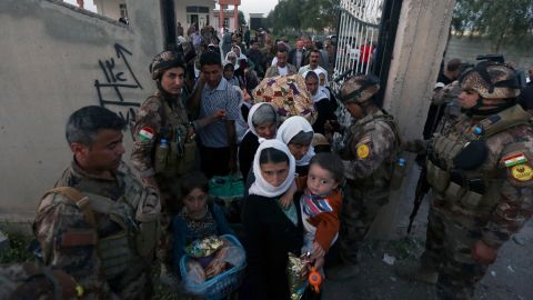 Kurdish Peshmerga forces help Yazidis as they arrive at a medical center in Altun Kupri, Iraq, on April 8.