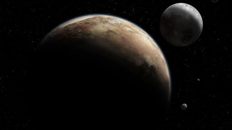 An artist's concept shows Pluto and its moons. Pluto's moon Charon has cracks that suggest it once had underground water.