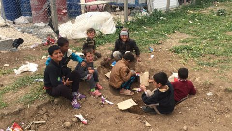 Children play in the dirt with toys crafted from cardboard. Some clamber through the wire fence and play with rocks -- anything to keep themselves entertained.
