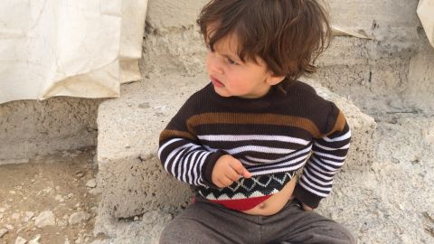 A small boy sits on the ground at Shariya refugee camp in Duhok, in Iraqi Kurdistan. It's home to thousands of Yazidis, many who fled from Mount Sinjar and surrounding towns when ISIS fighters moved in.