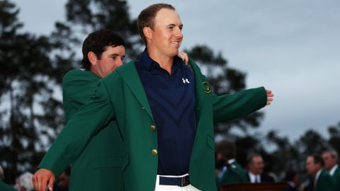 Defending champion Bubba Watson presents Jordan Spieth with the champion green jacket after he won the 2015 Masters Tournament on April 12 in Augusta, Georgia.