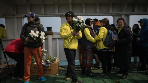 A relative hands out flowers to others on the deck of a boat during a visit to the site of the sunken ferry. More than 100 relatives of victims of South Korea's Sewol ferry disaster tearfully cast flowers into the sea.