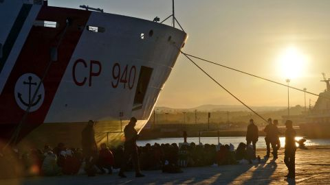 Shipwrecked migrants sit on the quayside after disembarking from a rescue vessel in the Italian port of Augusta in Sicily on April 16, 2015. As many as 41 migrants drowned after a small boat carrying refugees sank in the Mediterranean, Italian media said, days after 400 were lost in another shipwreck. Four survivors told Italian police and humanitarian organisations that their inflatable vessel sank not long after leaving the coast of Libya for Europe with 45 people on board. AFP PHOTO / GIOVANNI ISOLINO (Photo credit should read GIOVANNI ISOLINO/AFP/Getty Images)