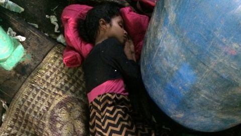 Muna's grandchild sleeps curled around an oil drum during the journey from Aden to Djbouti.