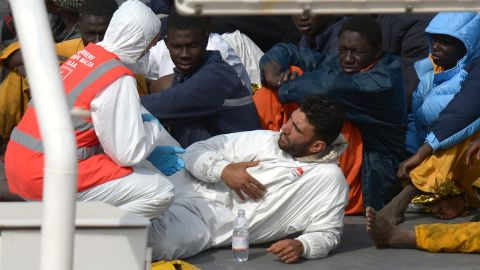 Rescued migrants talk to a member of the Malta Order after a fishing boat carrying migrants capsized off the Libyan coast on April 20, 2015.