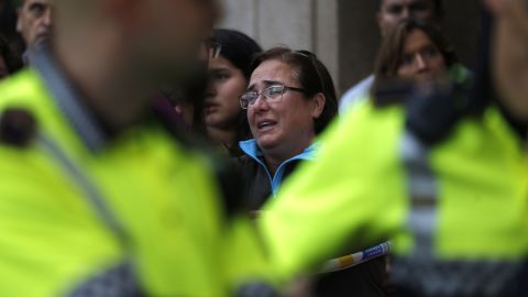 A woman reacts outside a high school in Barcelona after a teacher was killed.