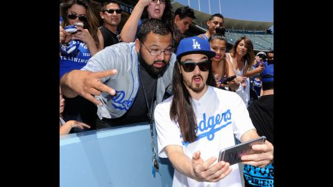 Musician Steve Aoki snaps a selfie with fans at a Los Angeles Dodgers baseball game on Sunday, April 19.