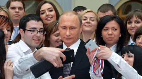 A man in Moscow takes a photo with Russian President Vladimir Putin on Thursday, April 16, after Putin's televised phone-in with the nation.