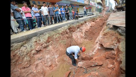 Workers move the fossilized eggs in Heyuan on April 19. They were carrying out road repairs when they found the eggs.