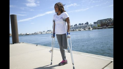 """<strong>Mery Daniel</strong>, a young mother from Haiti, was attending her second marathon when she was knocked to the pavement. She lost a leg, and the other leg was also damaged. She had pushed herself from ESL classes all the way to medical school, and instead found herself relearning how to walk with a prosthesis. She wears her """"Boston Strong"""" T-shirt proudly."""
