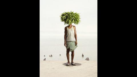 "Angad Ray, a flower seller, balances devdar leaves on his head. Photographer Ken Hermann visited the wholesale flower market Malik Ghat in Kolkata, India, for his project ""Flower Man."""