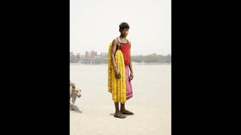 Chandan Kumar carries strands of gainda flowers on his shoulder.