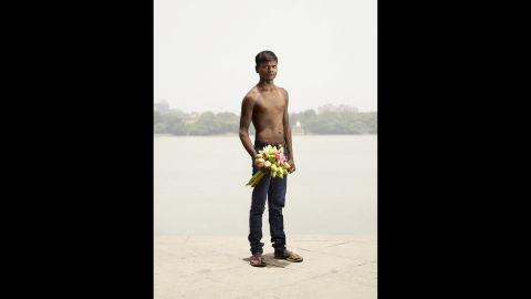 Flower seller Dev Kumar holds a bouquet of roses.