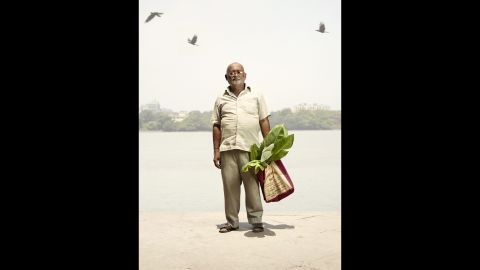 Prakash Singh stands for his portrait as birds are seen in the sky.
