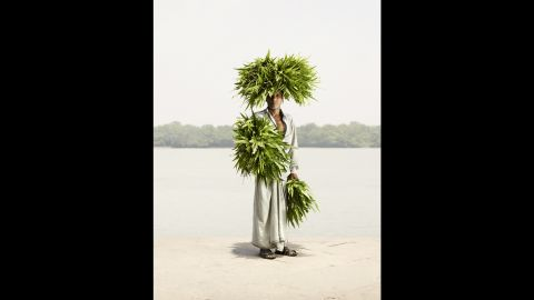 """The abundant leaves come to life in Odhir Gayen's portrait. """"These are a special kind of leaves, and many of (the sellers) carry them on their head and (on their) arms,"""" Hermann said. """"And when they walk around, it's almost like a human bush or something like that."""""""
