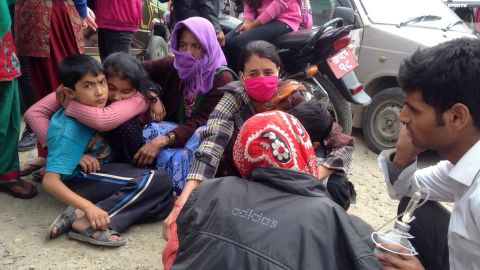 People huddle together outside a hospital in Kathmandu. Eyewitnesses said residents were scared and waiting for aftershocks to end.