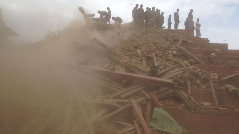 People help with rescue efforts at the site of a collapsed building in Kathmandu.