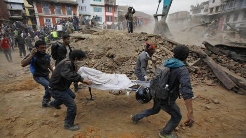 Volunteers carry a body recovered from the debris of a collapsed building in Kathmandu.