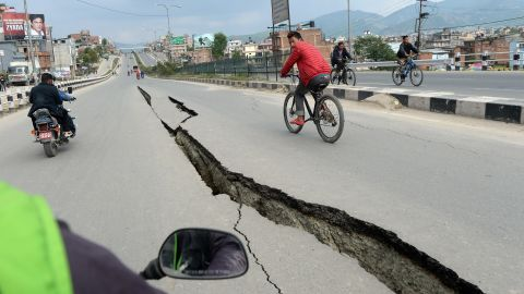 Residents cycle over damaged roads on the outskirts of Kathmandu on Sunday, April 26.