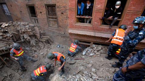 Nepalese military police search through rubble outside Kathmandu on April 28.
