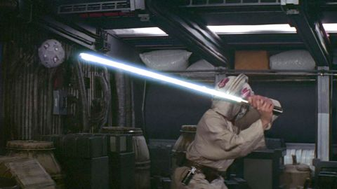 """Luke attempts to master the lightsaber, from the original """"Star Wars."""" The young Luke was encouraged to """"use the Force"""" to improve his feel with the weapon."""