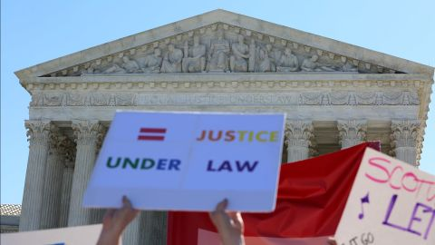 """Outside the Supreme Court of the United States, people hold signs calling for """"equal justice under law."""""""