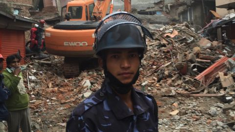 Nepal police officer Tejush Swarnakar stands in front of the rubble of what were six-storey guest houses.