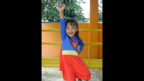 """Four-year-old Anthea Ballais of Tacloban, Philippines, is <a href=""""http://ireport.cnn.com/docs/DOC-979832"""">seen here</a> imagining herself soaring through the air as Supergirl."""