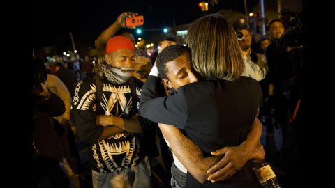 State Sen. Catherine E. Pugh embraces a protester while urging the crowd to disperse ahead of the 10 p.m. curfew.