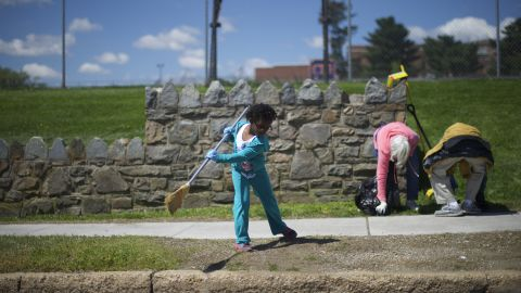 Kailah Johnson, 5, joins her mother in a neighborhood cleanup on April 28. Schools were closed across the city.