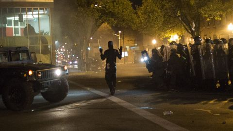 """A community organizer later identified as Joseph Kent paces in front of riot police with his hands up during a curfew in Baltimore on Tuesday, April 28. Moments later, he was seen being <a href=""""http://www.cnn.com/videos/us/2015/04/29/ctn-live-cuomo-baltimore-joseph-kent-arrested.cnn"""">arrested by police live on CNN</a>. Kent's lawyer said on April 30 that his client had been released from jail. While some protesters defied the curfew and faced off with police, demonstrations Tuesday were largely peaceful."""