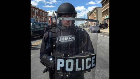 """At around noon, Larson took portraits of police officers in full riot gear, forming a line blocking North Avenue. """"We watched the police mass, from a few officers when we arrived to one hundred-plus over the span of an hour,"""" he said."""