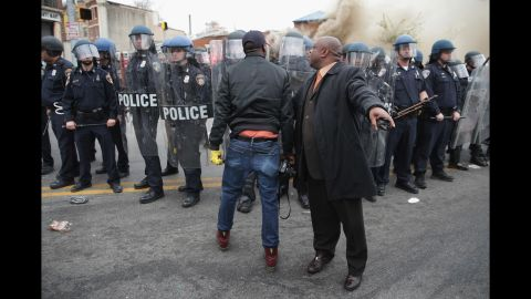 """A man attempts to calm a fellow demonstrator as they face police in Baltimore in April 2015. Riots broke out after <a href=""""http://www.cnn.com/2015/04/27/us/gallery/freddie-gray-funeral/index.html"""">the funeral for Freddie Gray</a>, who died of a severe spinal cord injury while in police custody. His death sparked <a href=""""http://www.cnn.com/2015/04/23/us/gallery/freddie-gray-protest/index.html"""">protests in Baltimore</a> and raised long-simmering tensions between police and residents."""