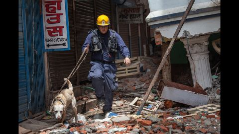 A member of the Los Angeles County Fire Department guides his sniffing dog through a collapsed building in Kathmandu on Thursday, April 30.