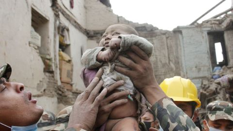 """In this Sunday, April 26, 2015, photo taken by Amul Thapa and provided by KathmanduToday.com, four-month-old baby boy Sonit Awal is held up by Nepalese Army soldiers after being rescued from the rubble of his house in Bhaktapur, Nepal, after Saturday's 7.8-magnitude earthquake shook the densely populated Kathmandu valley.  Thapa says that when he saw the baby alive after 20 hours of rescue efforts""""... all my sorrow went. Everyone was clapping. It gave me energy and made me smile in spite of lots of pain hidden inside me."""" (Amul Thapa/KathmanduToday.com via AP)"""