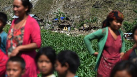 People await aid from an Indian army helicopter in front of damaged homes in Kulgaun, Nepal, on May 1.