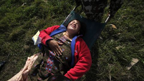An injured woman gets carried on a stretcher at Kathmandu's airport after being evacuated from Melamchi, Nepal, on May 1.