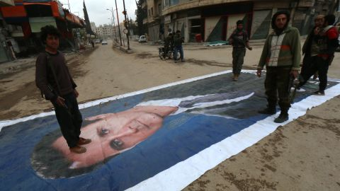 Fighters from a coalition of Islamist forces stand on a huge portrait of Syrian President Bashar al-Assad on March 29, 2015, in the Syrian city of Idlib, the second provincial capital to fall from government control.